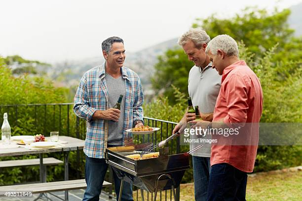 Friends having beer while barbecuing