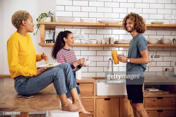 friends having breakfast in the kitchen at home - roommate stock pictures, royalty-free photos & images