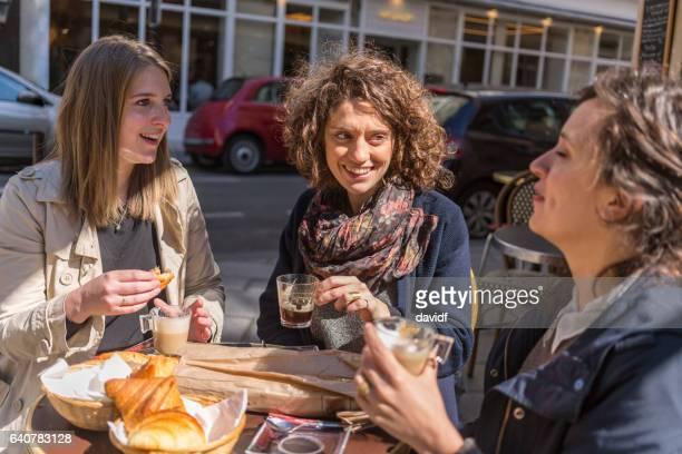 Amis, prenant son petit déjeuner ensemble dans un café Français