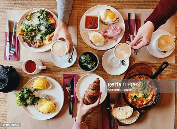 friends having brunch at the restaurant, high angle view - gourmet stock pictures, royalty-free photos & images