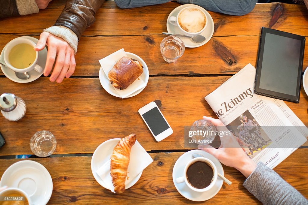 Friends having coffee and snacks at table : Stock Photo