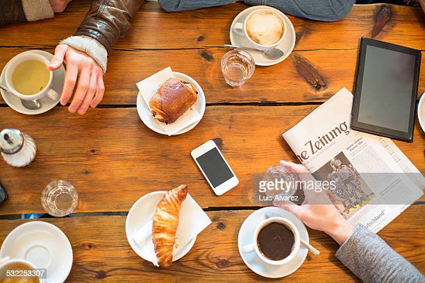 Friends having coffee and snacks at table