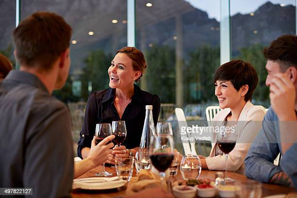 Friends having conversation over dinner with wine