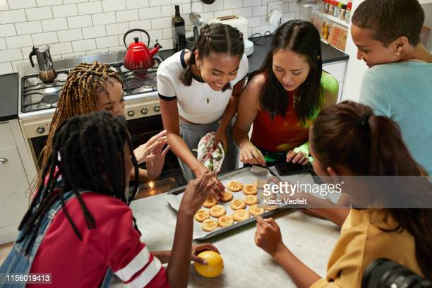 friends having cookies at kitchen - groupe moyen de personnes photos et images de collection