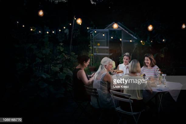 friends having dinner in garden - ストリングライト ストックフォトと画像