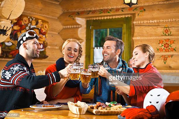 Friends having dinner in restaurant, toasting with beer