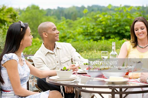 friends having dinner outside on a patio. - cef do not delete stock pictures, royalty-free photos & images