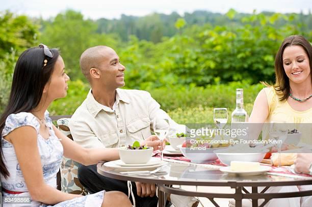 "friends having dinner outside on a patio. - ""compassionate eye"" fotografías e imágenes de stock"