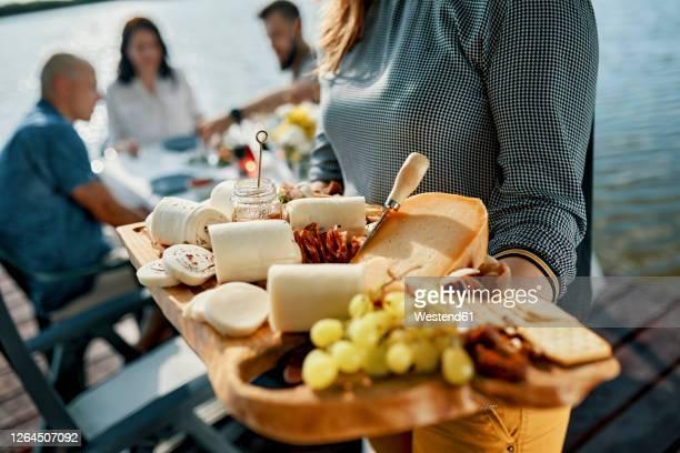 friends having dinner with a cheese platter at a lake - kaasplank stockfoto's en -beelden