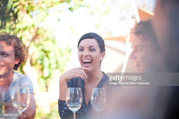 Friends having drinks at table outdoors