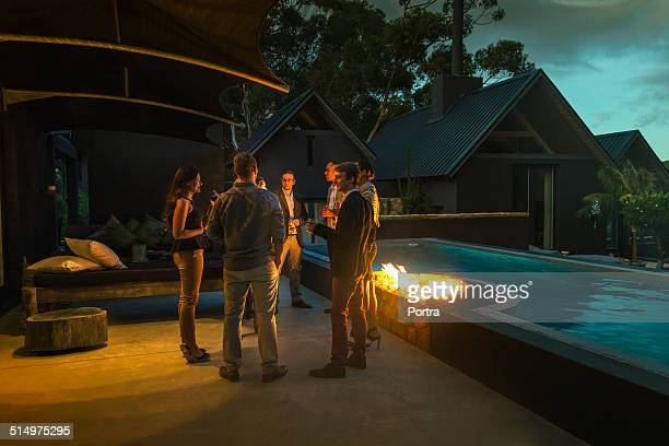 friends having drinks by fireplace at poolside - man on fire stock photos and pictures