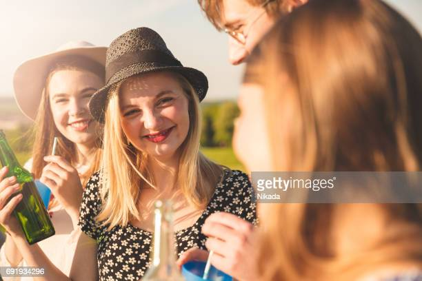 Friends having drinks in picnic on sunny day