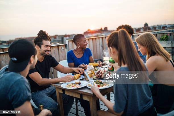 friends having food at rooftop party - barbecue social gathering stock pictures, royalty-free photos & images