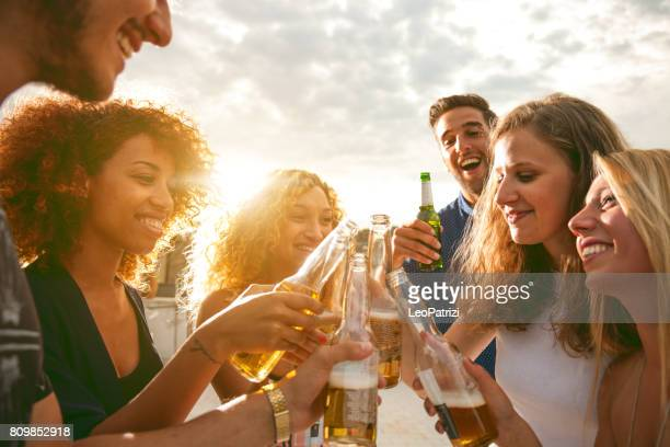 friends having fun and drinking beer at birthday party - aperitif stock photos and pictures