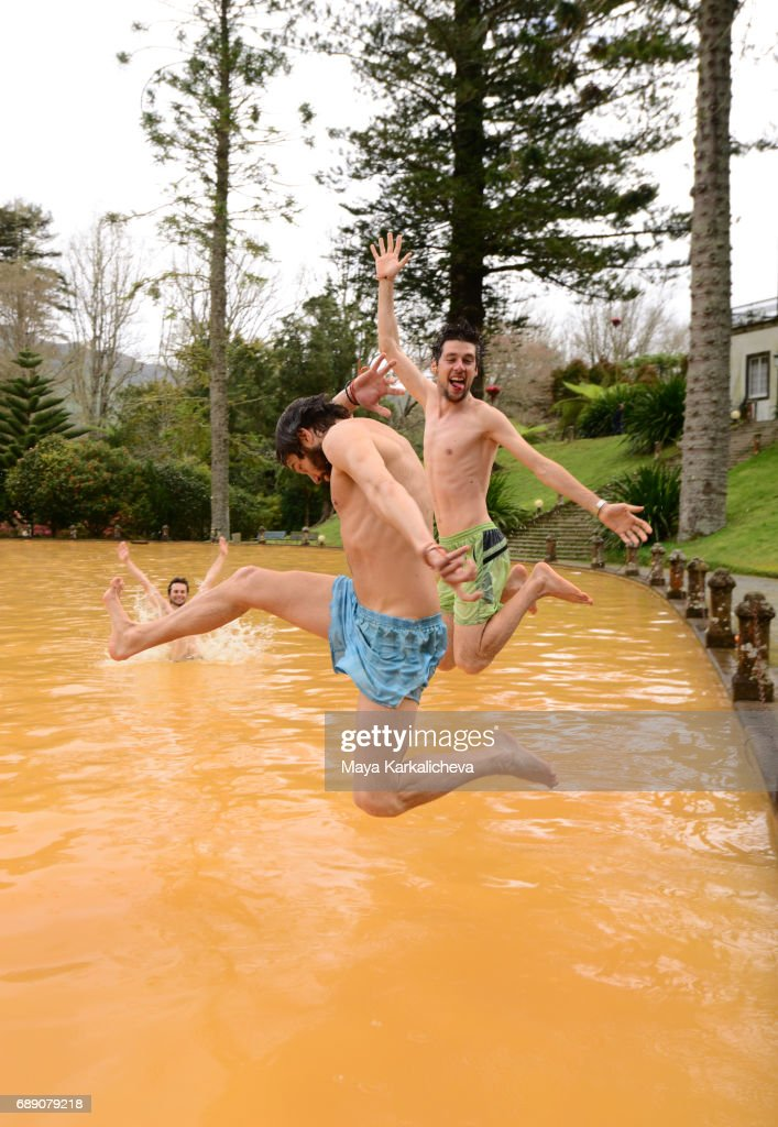 Friends having fun and jumping into volcanic hot springs : Stock Photo