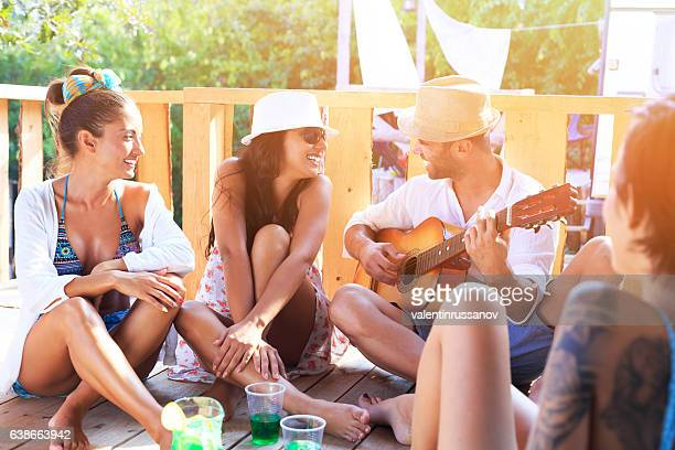 Friends having fun and playing guitar on pavilion