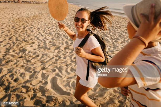 vrienden die pret bij strand hebben - racket sport stockfoto's en -beelden