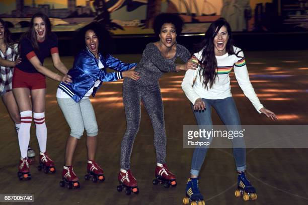 friends having fun at roller disco - volgen activiteit stockfoto's en -beelden