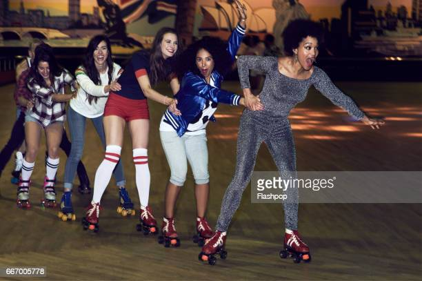 friends having fun at roller disco - following stock pictures, royalty-free photos & images