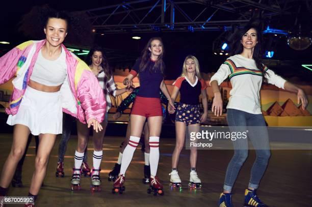 friends having fun at roller disco - eislauf oder rollschuhlauf stock-fotos und bilder