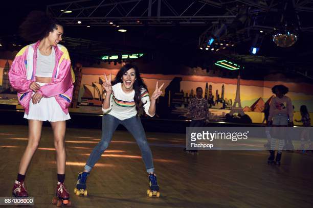 friends having fun at roller disco - roller skating stock photos and pictures