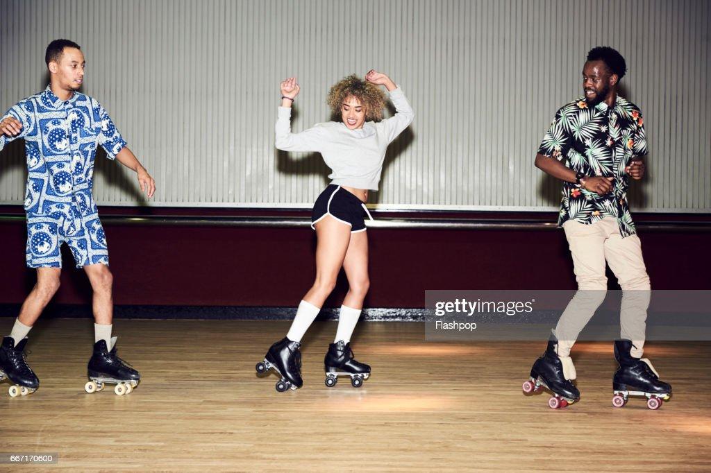 Friends having fun at roller disco : Stock Photo