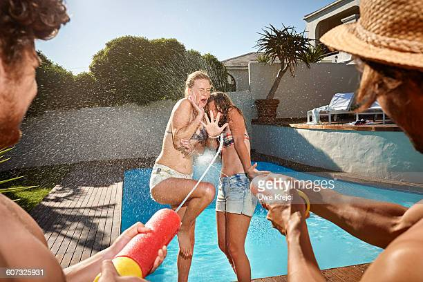 Friends having fun by swimming pool