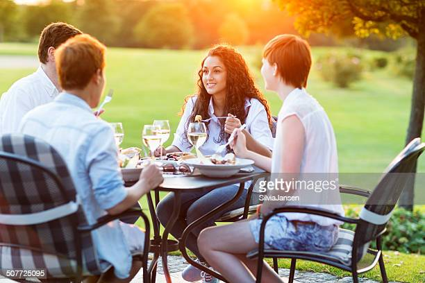 friends having fun  dinner together at beautiful summer evening
