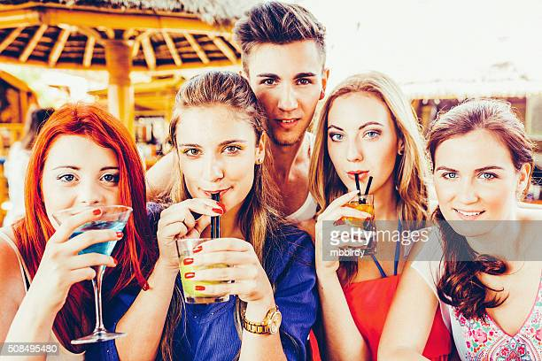 Friends having fun drinking cocktails at party