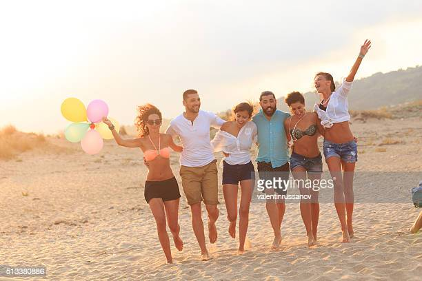 Friends having fun on beach with baloons