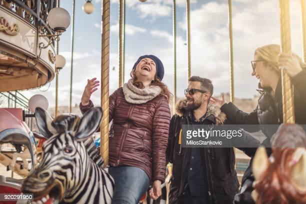 Friends having fun on Carousel at Paris
