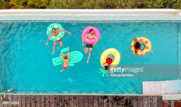 friends having fun on inflatable rings in the pool - inflatable ring stock pictures, royalty-free photos & images