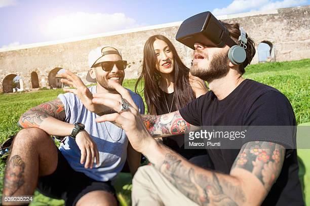 Al aire libre amigos divirtiéndose en el parque con auriculares VR