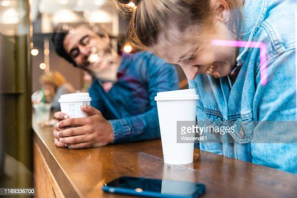 friends having fun together in a coffee shop - daten stockfoto's en -beelden