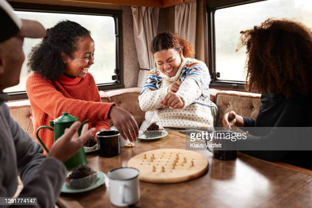 friends having fun while playing board in motor home - chequers stock pictures, royalty-free photos & images