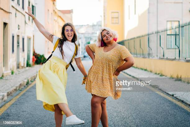 friends having fun while standing on road in city - body positive stock pictures, royalty-free photos & images