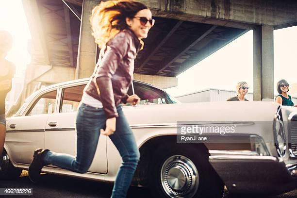 Amigos divirtiéndose con coche clásico