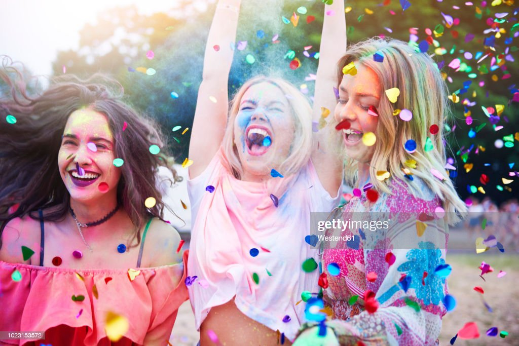 Friends having fun with holi powder and confetti : Stock Photo