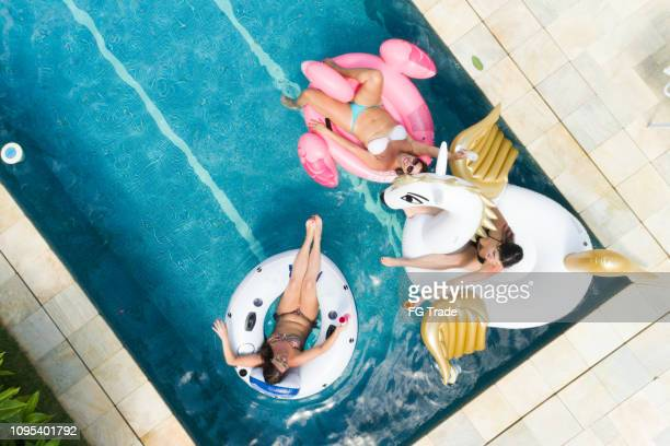 friends having fun with inflatable float at swimming pool - aerial view - pool party stock pictures, royalty-free photos & images