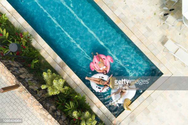 friends having fun with inflatable float at swimming pool - aerial view - piscina foto e immagini stock