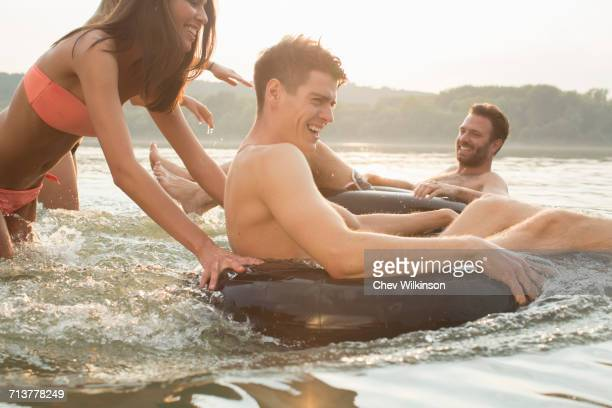 friends having fun with inflatable ring in river - inflatable ring stock pictures, royalty-free photos & images
