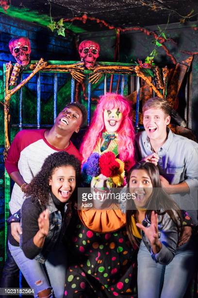 friends having fun with zombies in haunted house - scary clown makeup stock photos and pictures
