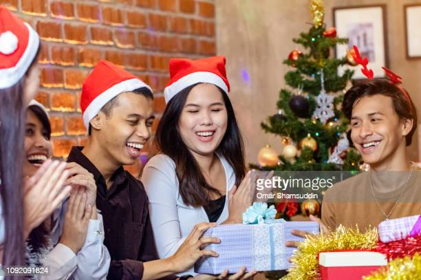 Friends having good time while exchanging gifts