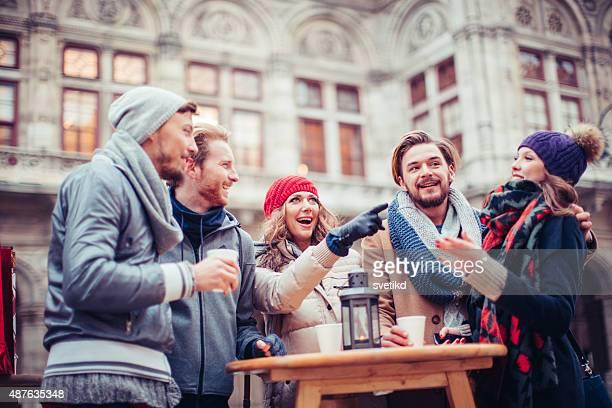 Friends having hot drinks outdoors in winter city.