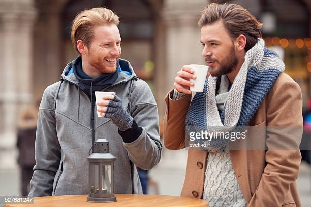 Friends having hot drinks outdoors in winter city.