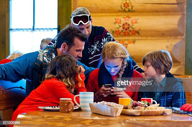 Friends having lunch after skiing, using a smart phone
