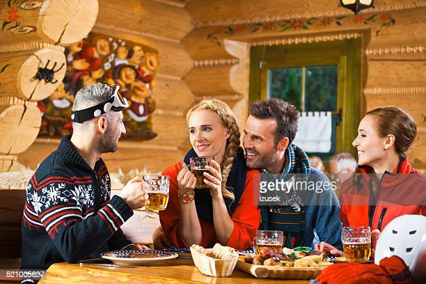 Friends having lunch and drinking beer after skiing