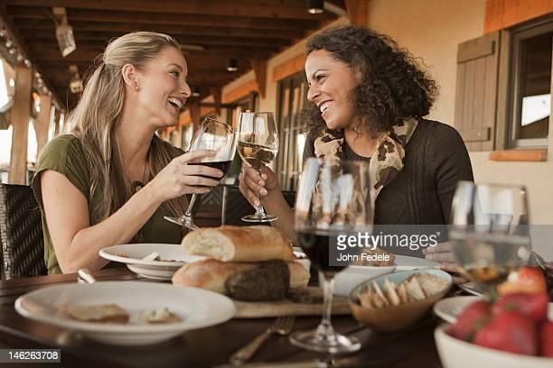 Amici avendo pranzo e bere vino insieme