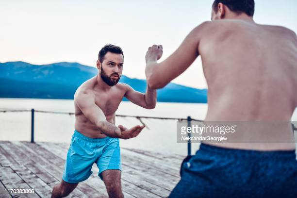 friends having martial arts training by the lake - boxing shorts stock pictures, royalty-free photos & images