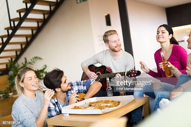 friends having party with pizza, beer and good music - saiteninstrument spielen stock-fotos und bilder